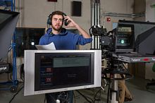 picture of a Centennial College broadcasting program student in an on-campus studio listening to the audio feed from a television broadcast