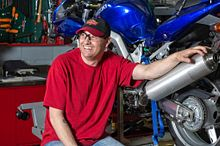 picture of a continuing education student in the garage smiling sitting next to his motorcycle.