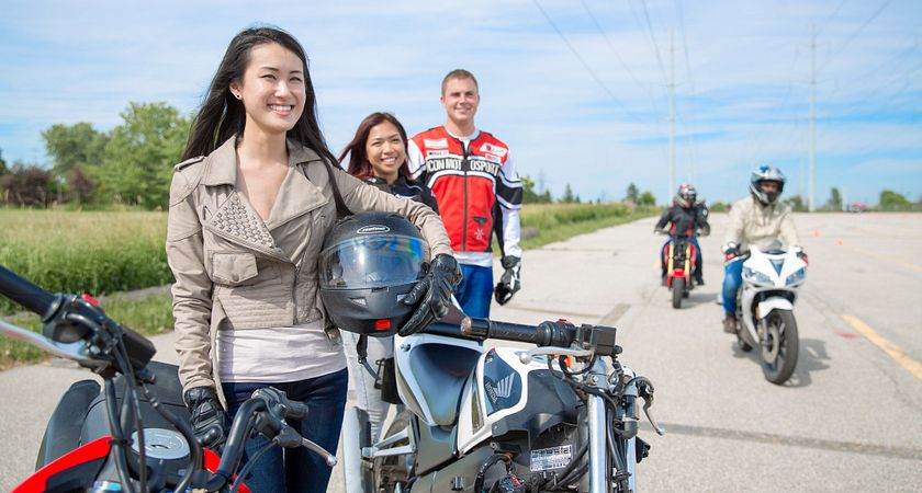 Picture of three students standing in a line with two motorcycles in the forefront. Two students are riding in the background