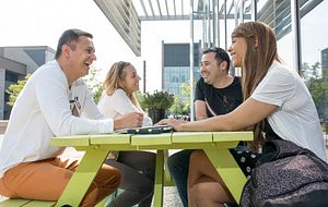 picture of centennial college students sitting at a picnic table in the progress campus courtyard