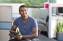 Picture of a Centennial College student at the Centre of Entrepreneurship sitting and smiling at the camera