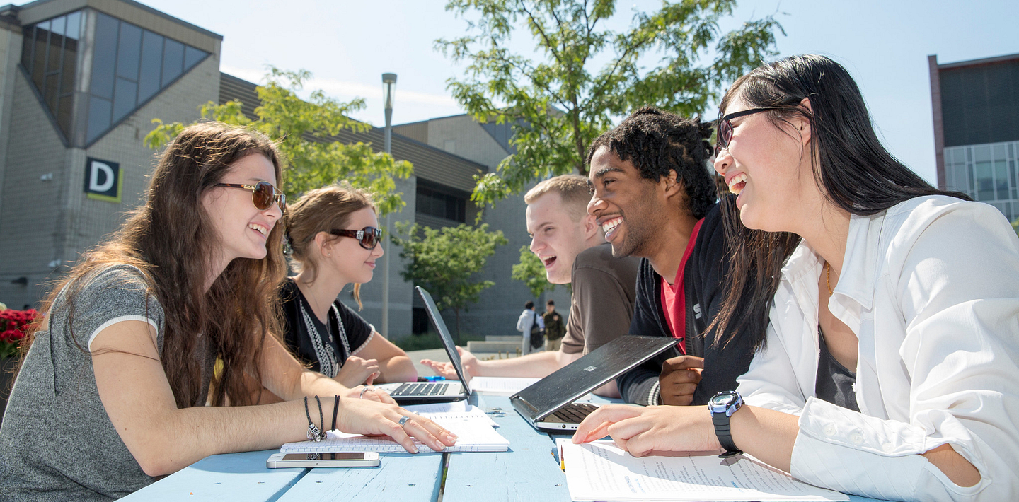 picture of Centennial College students talking and smiling at a picnic table in the Progress Campus courtyard
