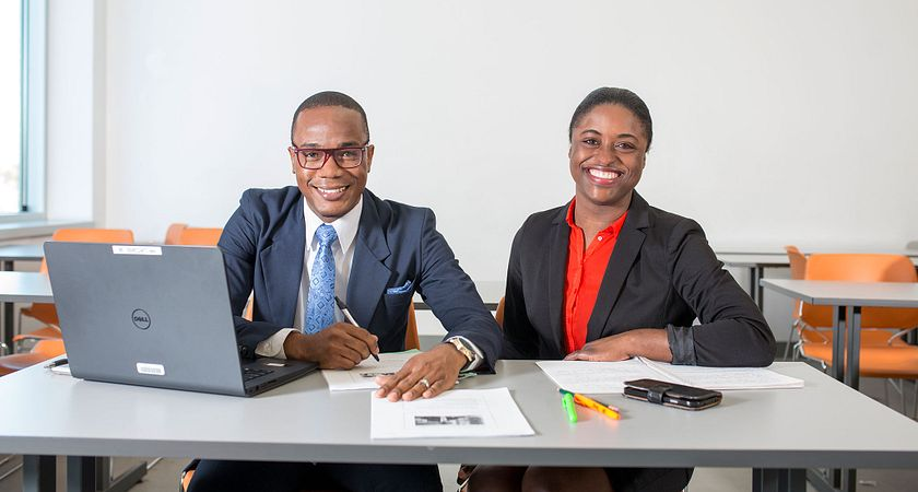 Picture of two Centennial College part-time business program students working at a desk