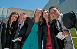 picture of Centennial College students at their convocation ceremony dressed in graduate gowns outside smiling