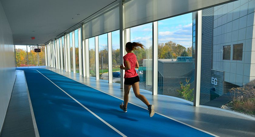 picture of a centennial college student running on the indoor track in the athletic and wellness centre at progress campus