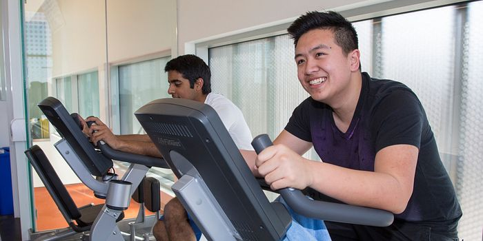 Picture of two Centennial College students in the Ashtonbee Campus gym cycling on exercise bikes and smiling