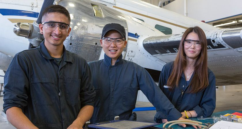Picture of Centennial College Aviation Technician Avionics Maintenance program students in the hanger working on an airplane