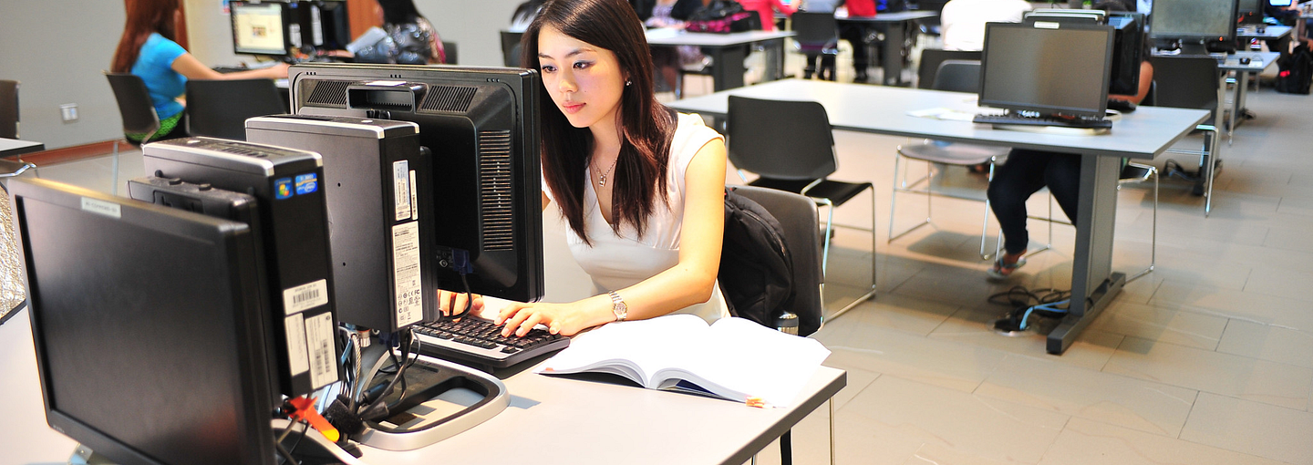 Students on computers in the library