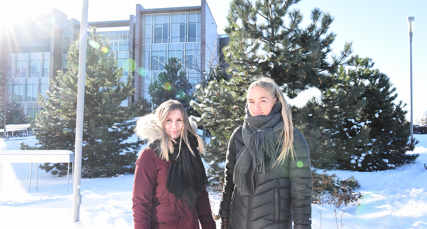 Two female students wearing winter jackets and standing in front of the Progress library building during winter