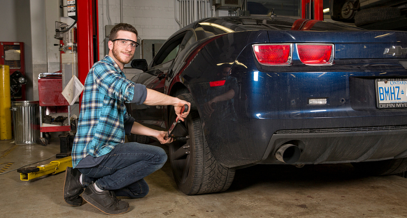 Picture of a male student working on car in the Chrysler/Fiat lab