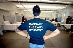 Massage therapy student puts hands on waist as he poses his back to the camera and his shirt saying Massage Therapy Student