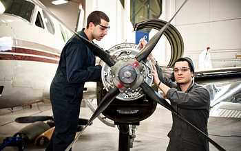 Two aviation students working on an airplane