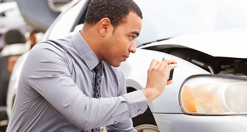 Photo of an insurance assesor inspecting a vehicle