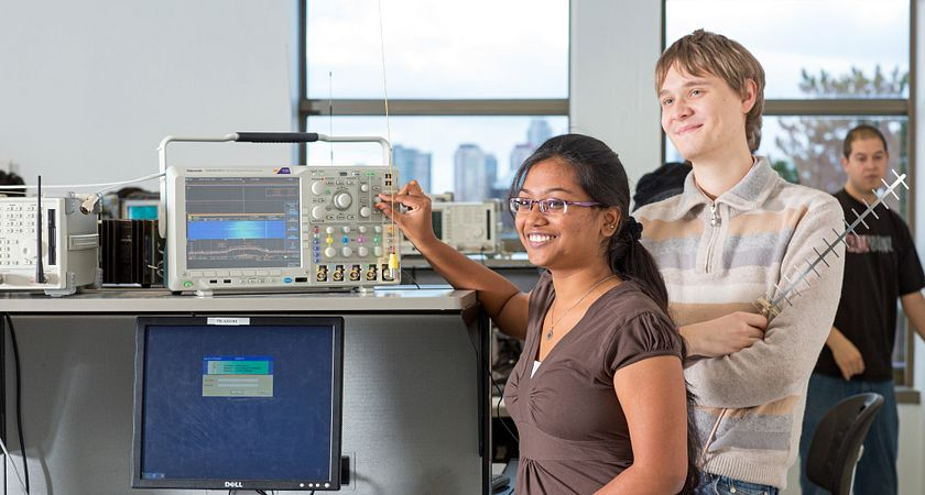 picture of two Centennial College Electrical Engineering Technician program students in a computer lab working with electronics