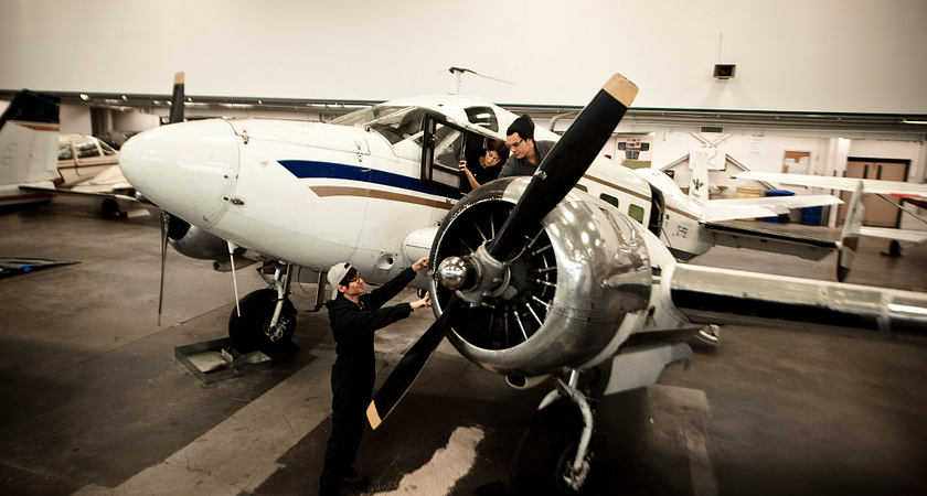 picture of Centennial College Aviation Technician program students working on an airplane in a hangar at Ashtonbee Campus