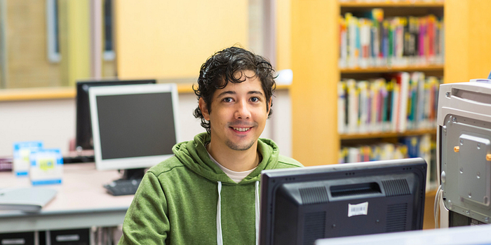 Picture of a Centennial College student in the Story Arts Centre library working on a computer