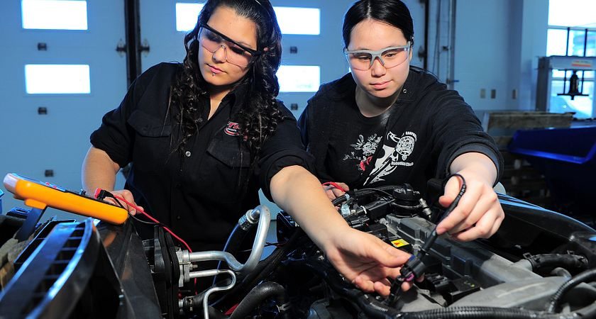 Photo of two female transportation students monitoring a car engine using an analysis tool.