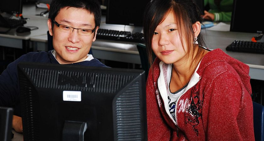 Two English as a second language learners sitting down in the computer lab