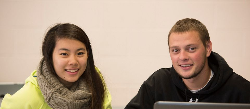 Picture of a centennial college student peer tutor helping another student