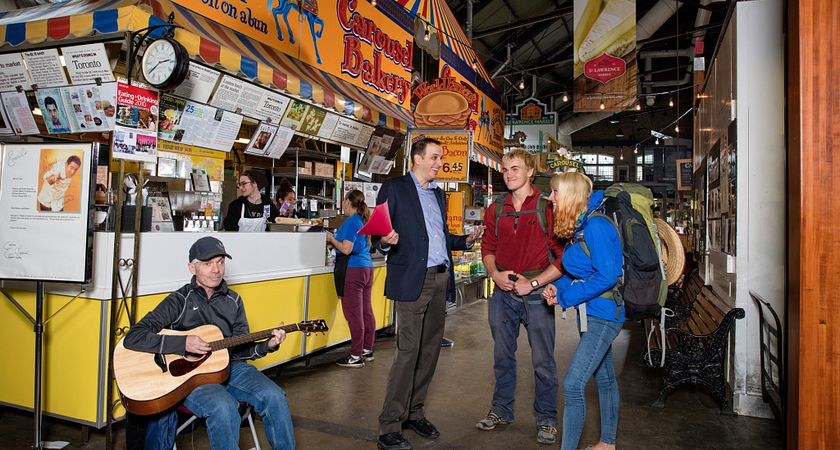 picture of two food tourists in a food market speaking with a food tour guide