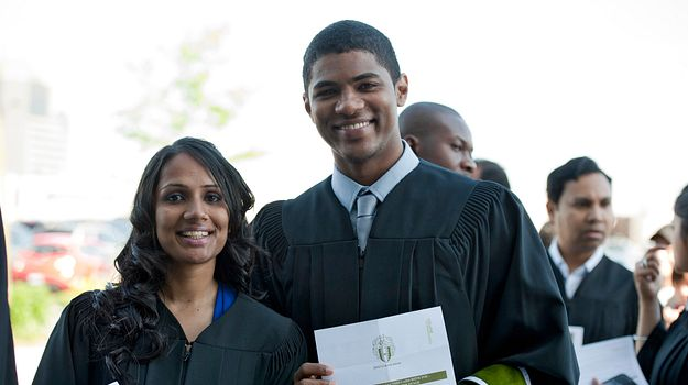 Picture of two graduates in their gowns at convocation