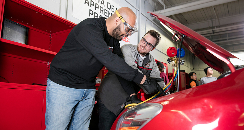 picture of two Centennial College Automotive Parts and Service Operations program students working on a car under the hood in a garage