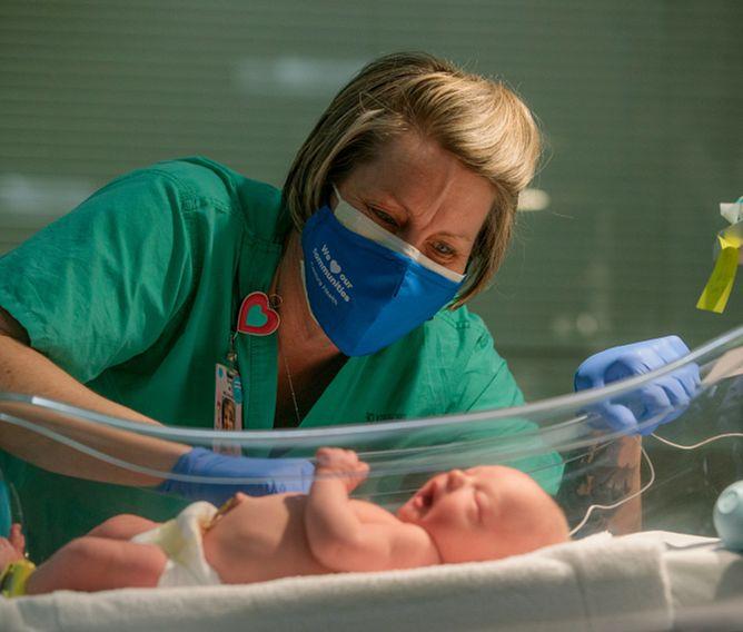 Ollie Campbell, RN caring for newborn in NICU
