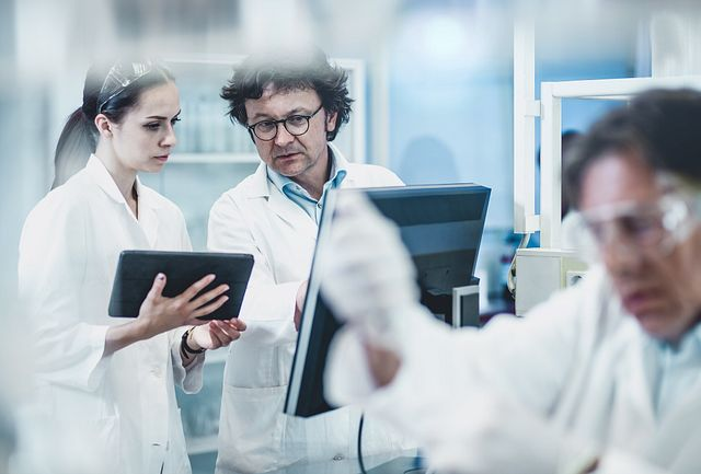a male and female scientist, dressed in white lab coats, looking at a computer screen in a lab