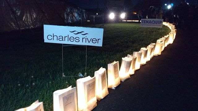 Charles River sign with lighted luminarias at Relay for Life event to support the American Cancer Society