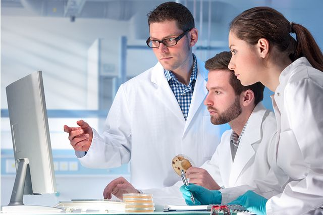 three scientists in lab coats looking at computer screen analyzing results