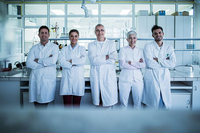 Team of scientists wearing white lab coats from Charles River Massachusetts standing in front of the lab.
