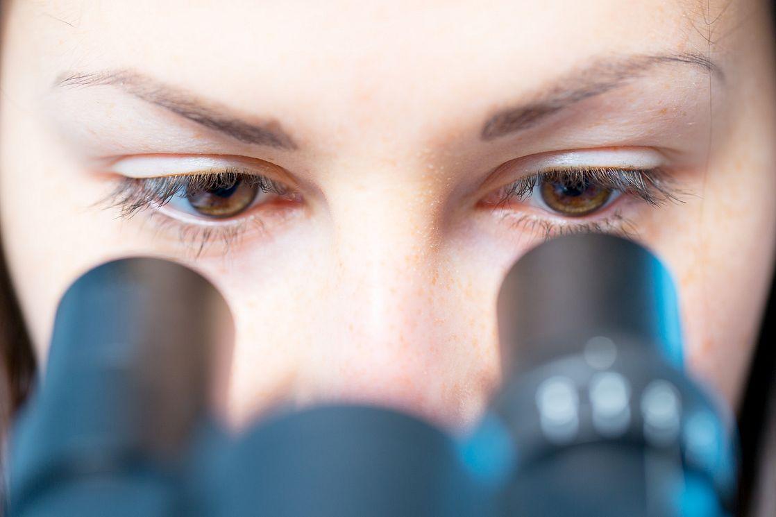 female scientist using a microscope