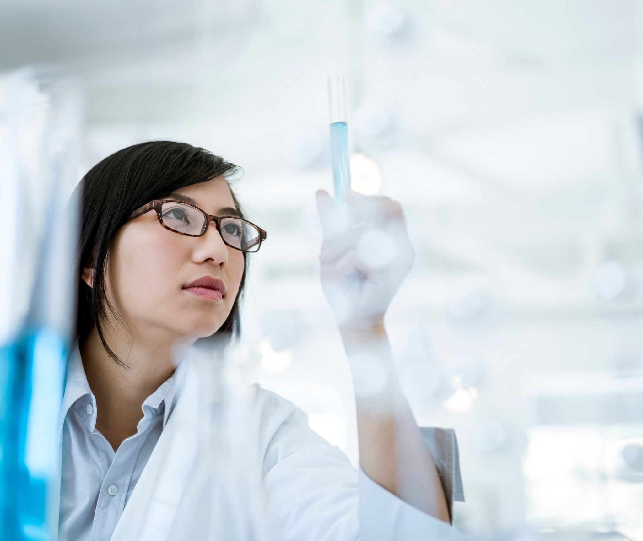 Scientist with glasses in a lab coat looking at a test tube full of blue liquid.