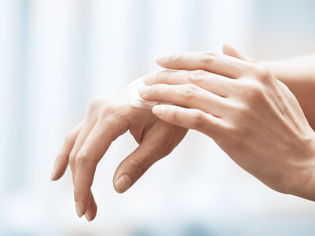 Hands rubbing medication on skin inflammation.