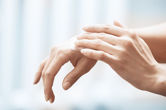 Female hand rubbing on lotion.