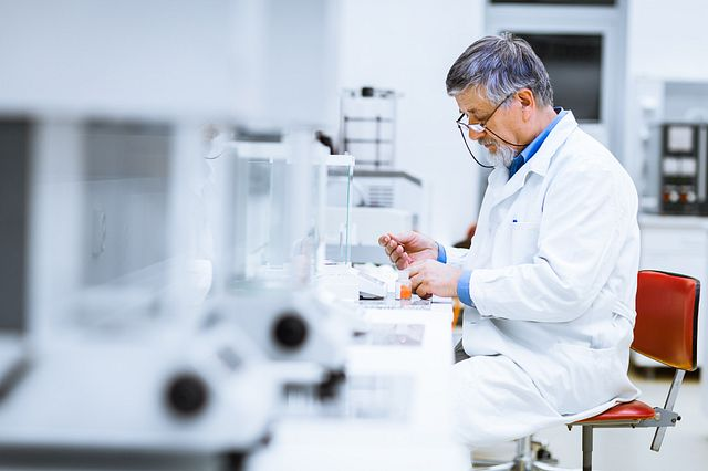 male scientist seated, working in a laboratory