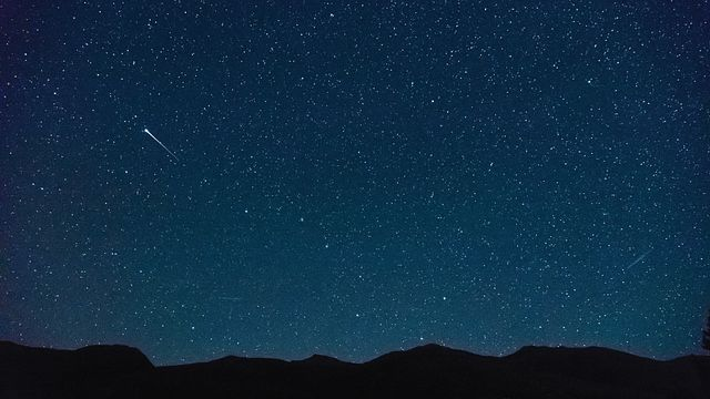 a falling star in the night sky, with mountain peaks on the horizon