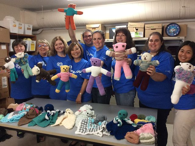 employees holding stuffed animals dressed in outfits they knitted as part of Charles River's One Day volunteer initiative