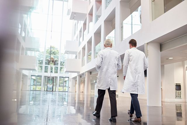Two scientists walking through the corridors of the laboratory consulting and collaborating to determine the best pathway forward for your drug development program