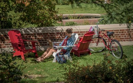 a student sitting in an adirondack chair on campus