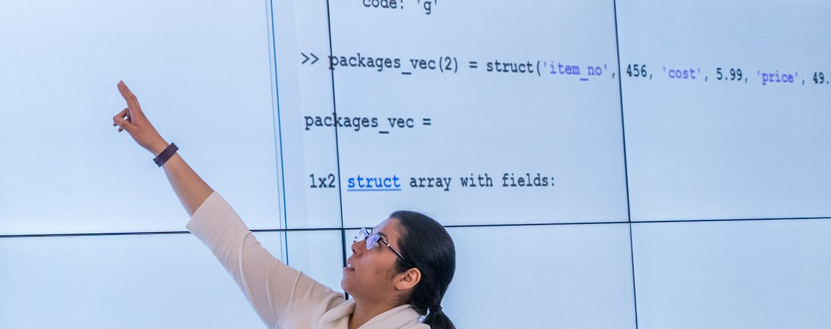 Student presenting with code on screens behind her
