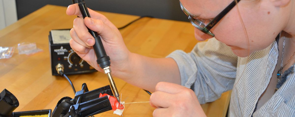 A student uses a soldering iron to connect parts of her project.