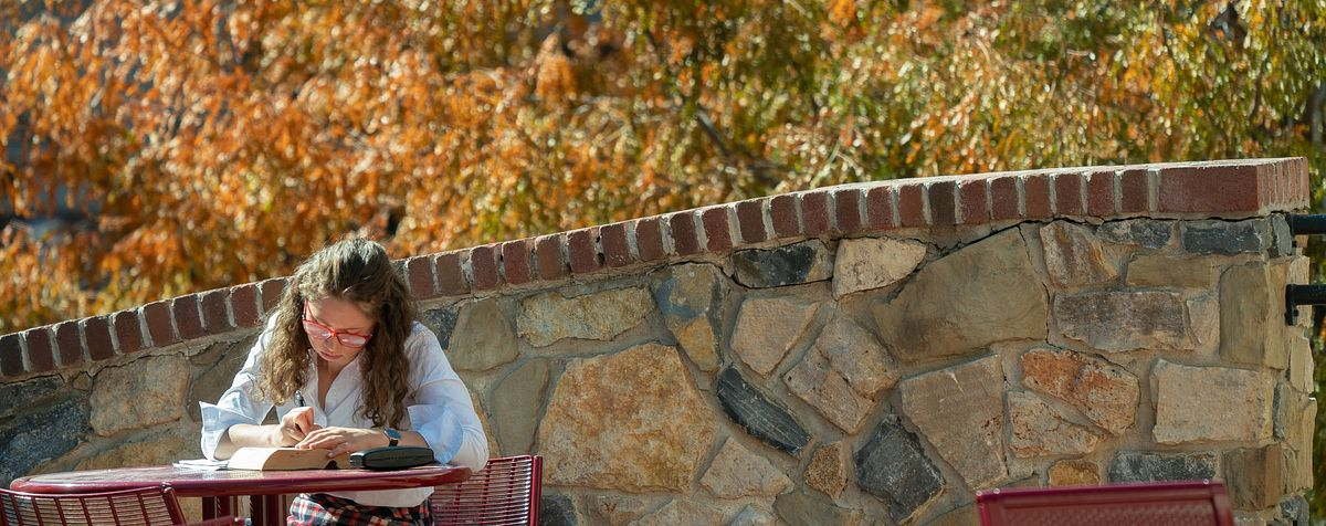 student working with book at outdoor table on DU campus