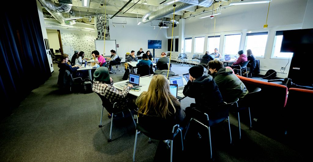 Students gathered around tables in he Cloud EDP Program space on DU's campus