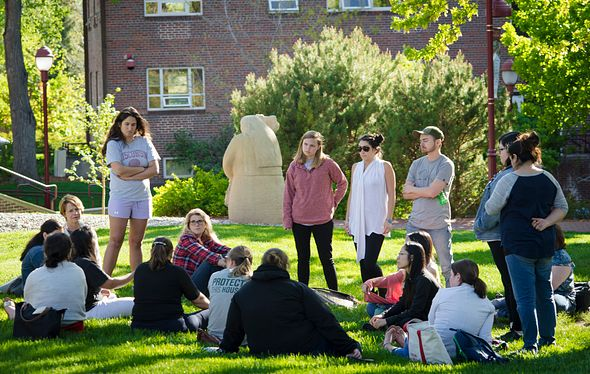 a group of students sitting and standing outside