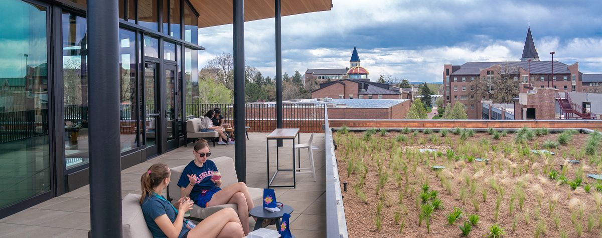 students sit on the deck of DU's community commons