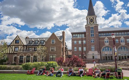 students working in adirondack chairs in front of DU buildings