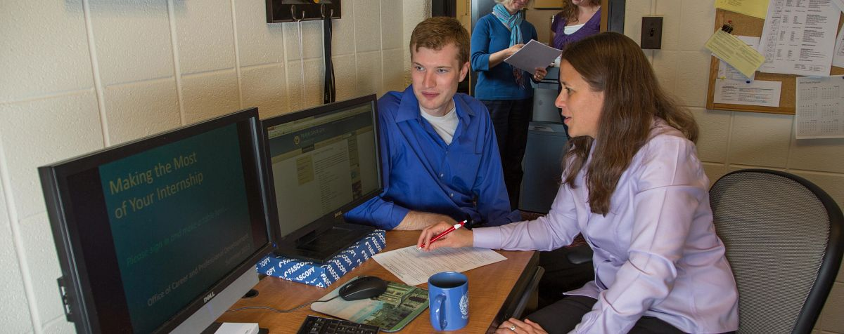 school counsler talks to student at a computer desk
