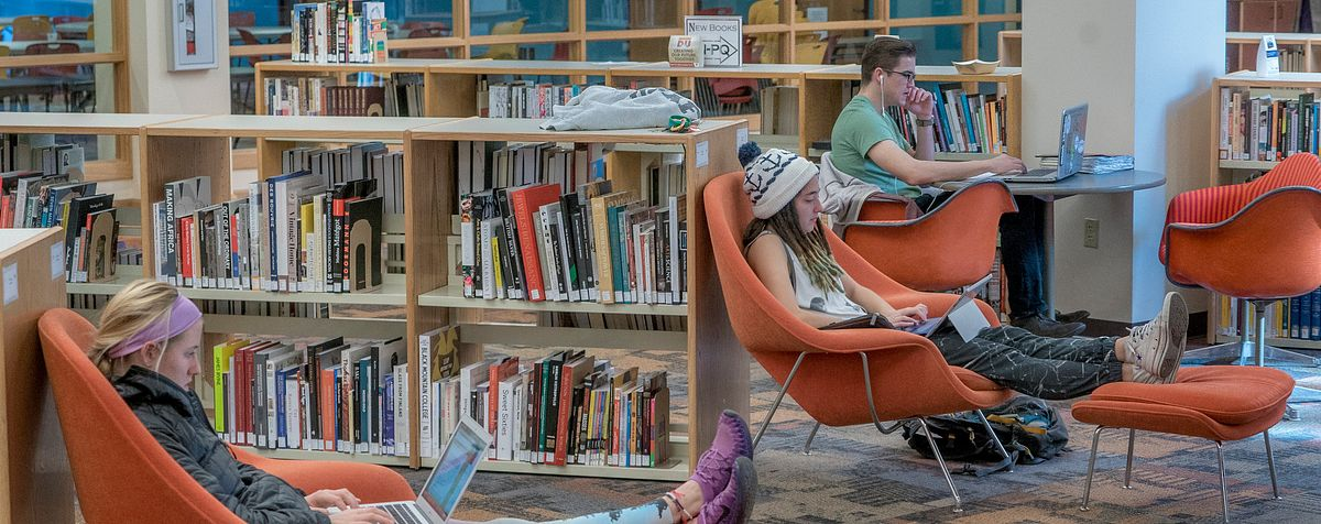 students working in library near bookshelves