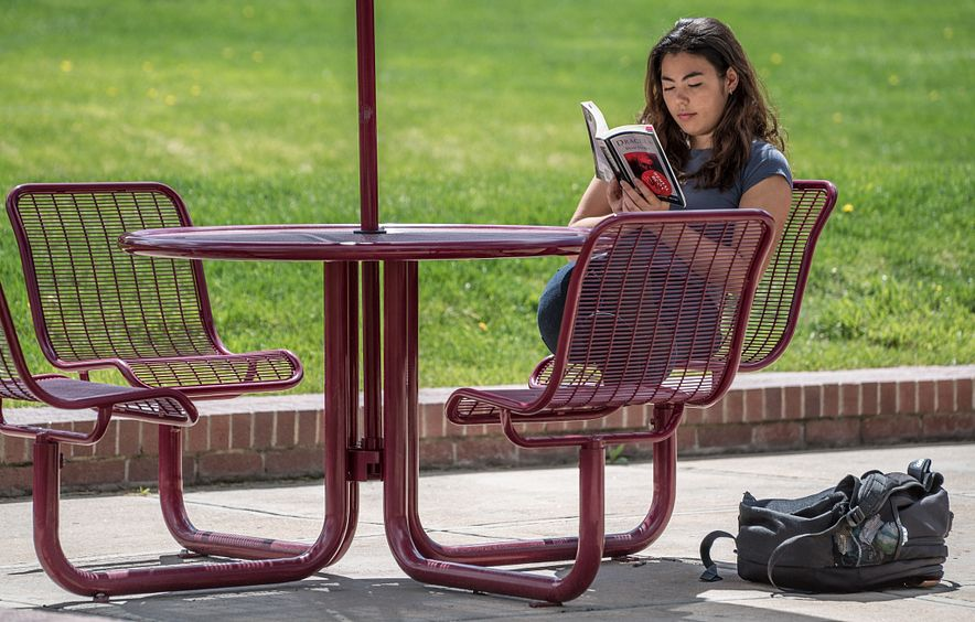 student seated at outdoor table on DU campus reading a book